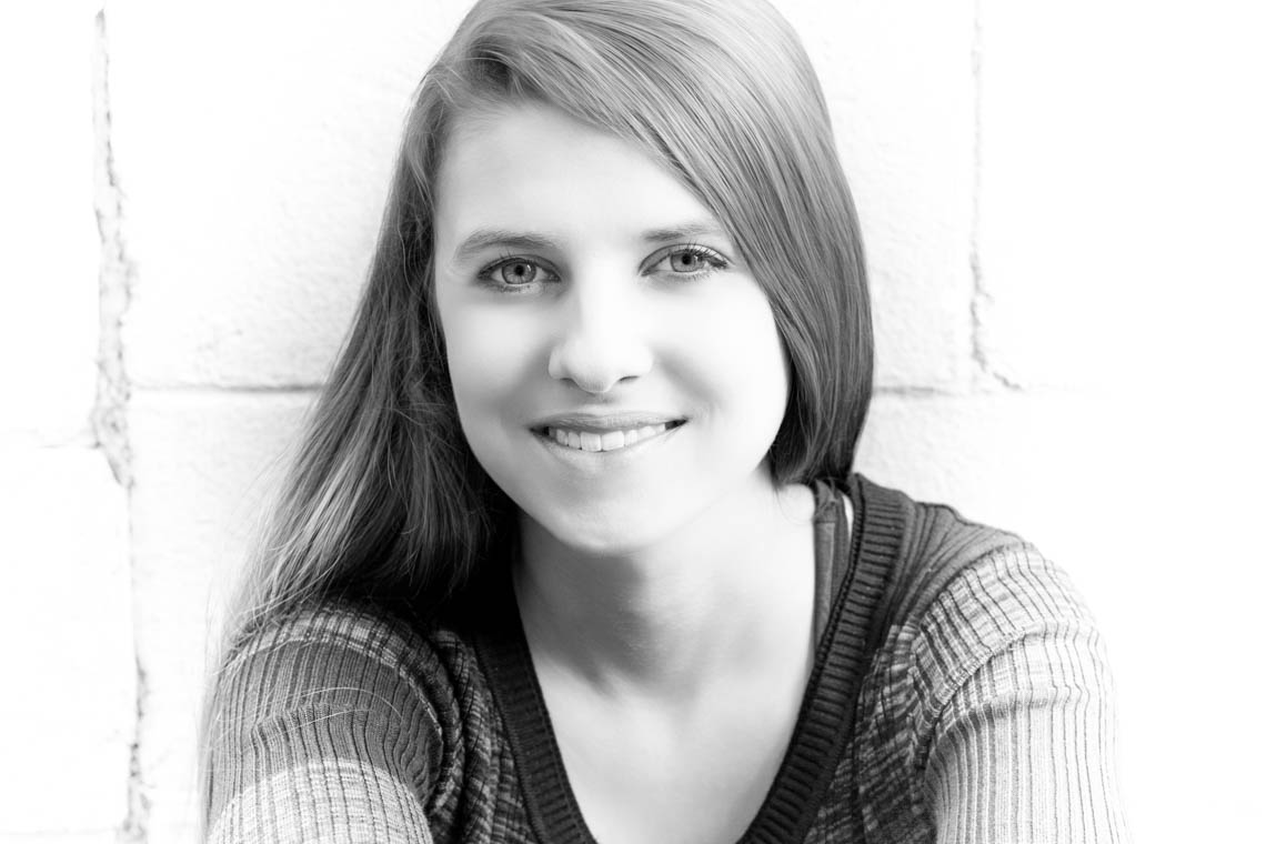 Black & White image of Allie sitting in front of a cinder block wall