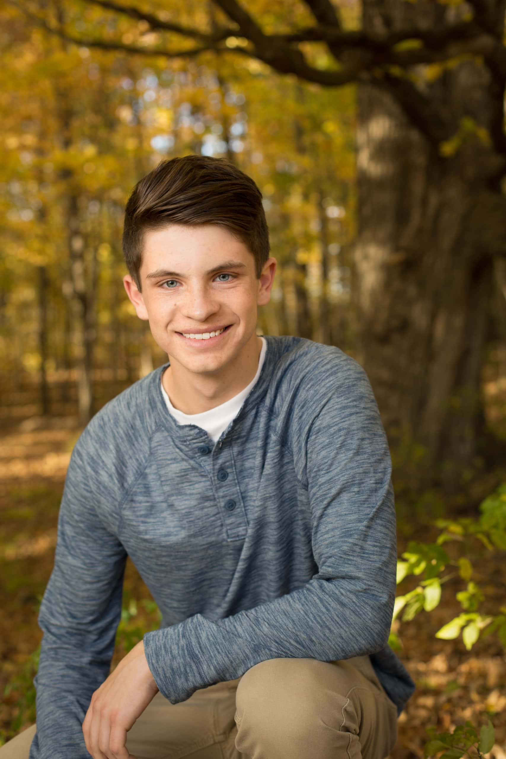 Ben sitting near the trunk of a tree with fall foliage behind him