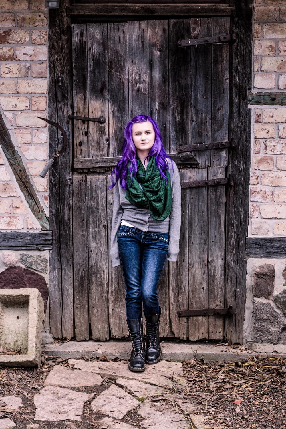 Carolyn standing in front of a weather worn wooden door at Monches Farm