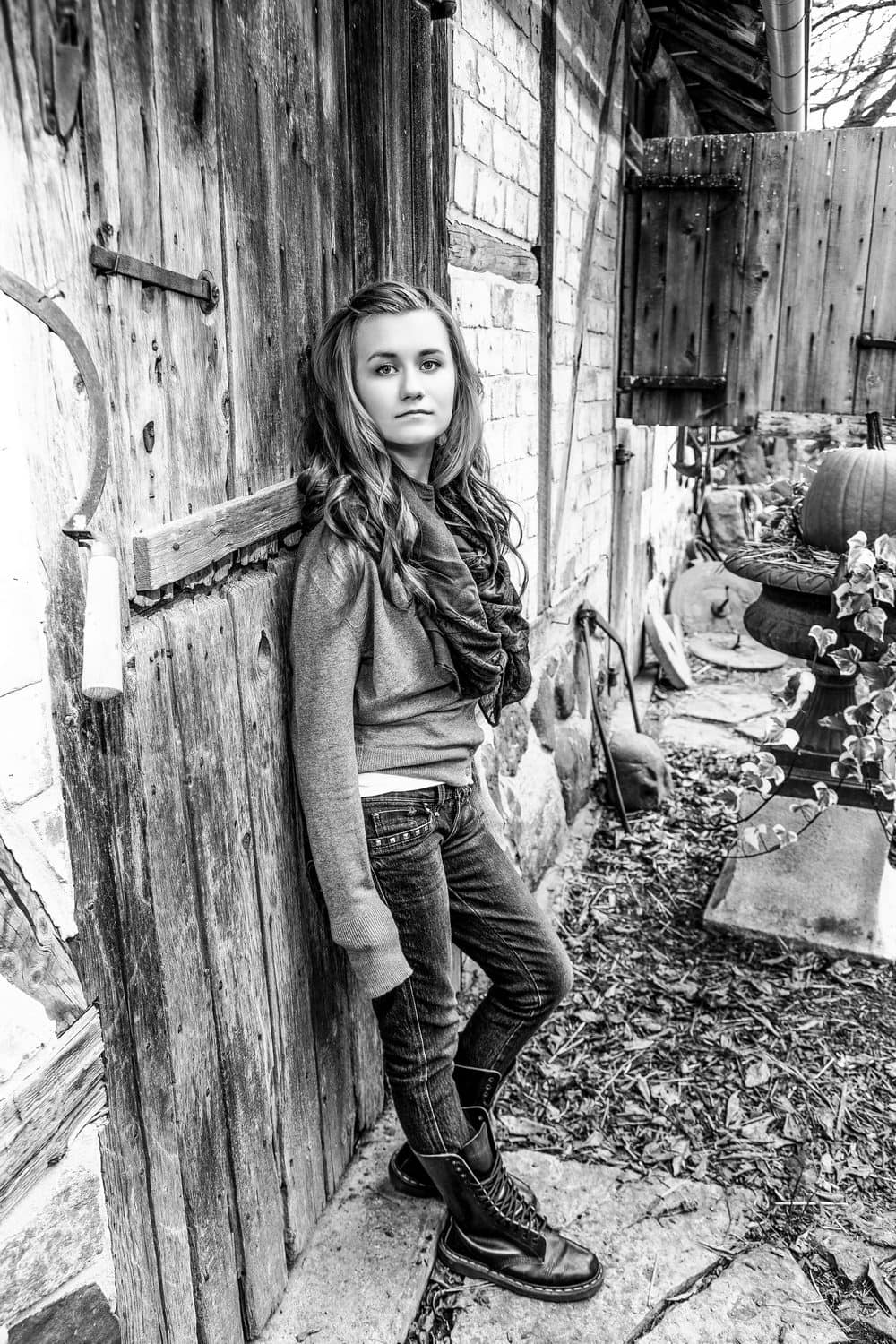 Black & White image of Carolyn standing in front of a weather worn wooden door at Monches Farm