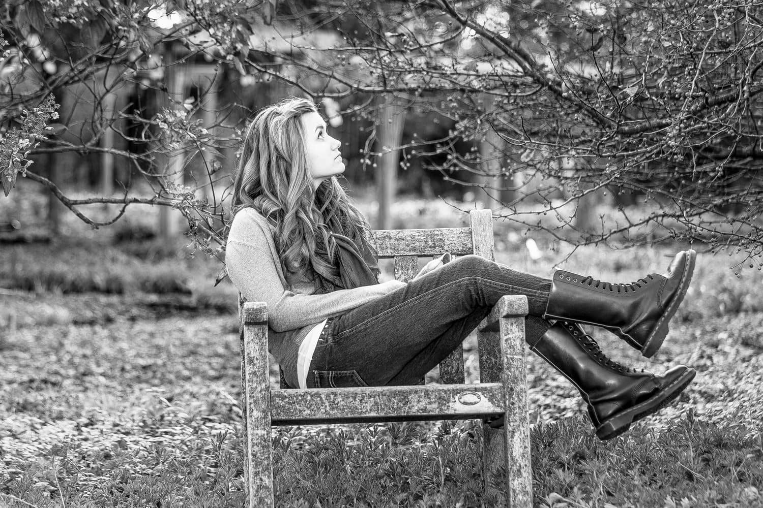 Carolyn sitting sideways in a wooden chair, outdoors at Monches Farm