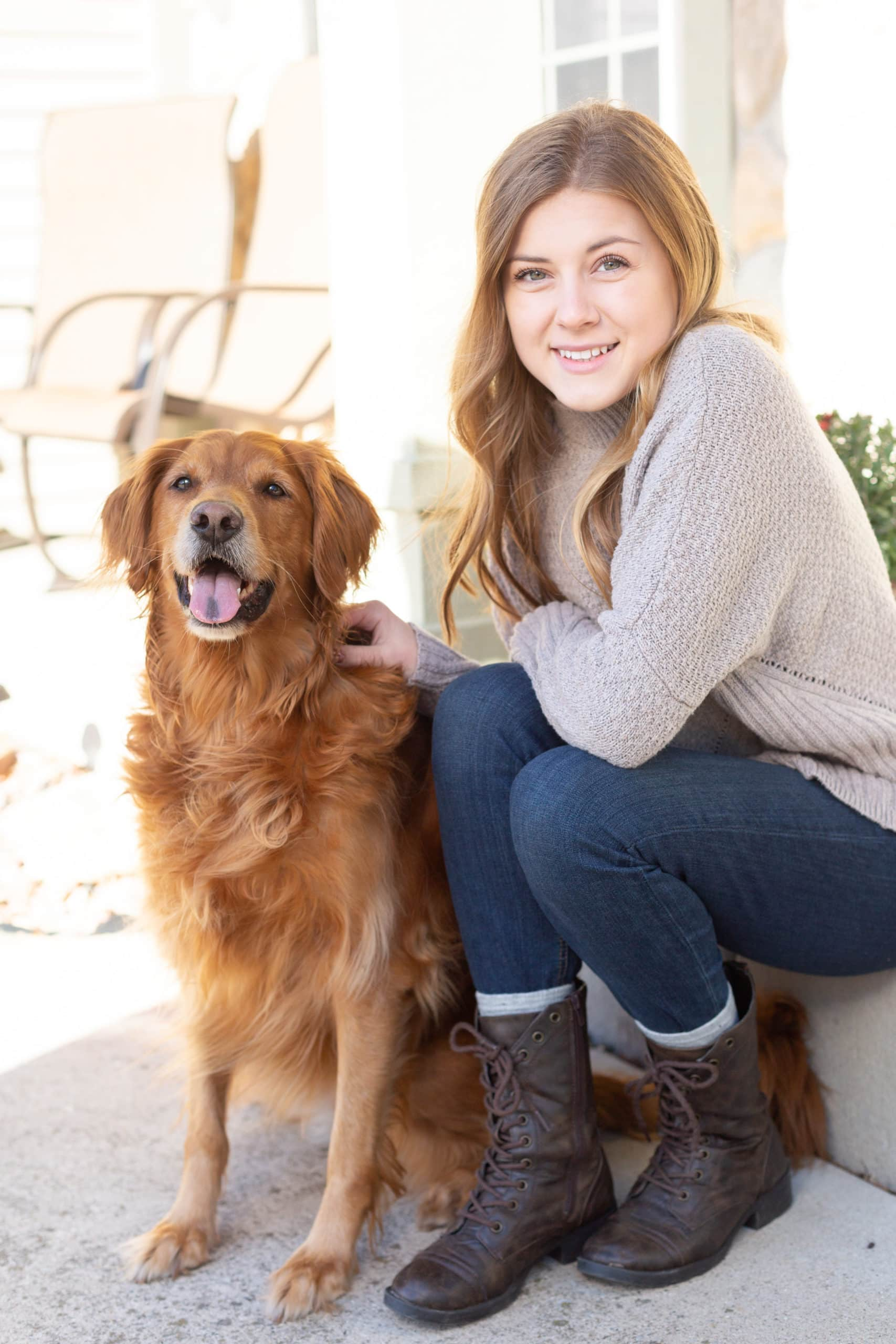 Maggie sitting in front of her house with a Golden Retriever